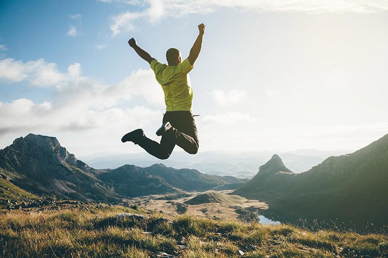 Tepede bir zaferle zıplayan adam